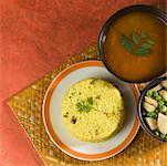 Erhöhte Ansicht von Reis auf einem Teller mit daal und gebratene Erbsen und Kartoffel-Scheiben in eine Schüssel geben