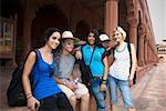 Three young women smiling with their friends, Taj Mahal, Agra, Uttar Pradesh, India