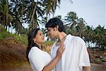 Jeune couple face à face sur la plage, Goa, Inde