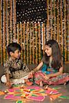 Boy and his sister making rangoli