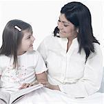 Mid femme adulte avec sa fille assise sur le lit et souriant
