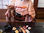 Woman wearing kimono eating sushi with chopsticks