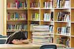 Étudiant en entouré de pile de livres de bibliothèque