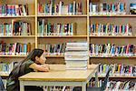 Étudiant en bibliothèque, en regardant la pile de livres