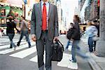 A businessman standing by a pedestrian crossing