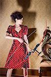 une femme fanshionable avec un arc et des flèches dans ses mains