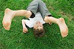 Junge mit Beinen in der Luft, auf dem Boden liegend lächelnd in die Kamera, erhöhte Ansicht
