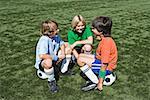 Jungs sitzen auf Fußbälle