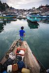 Homme avec des Articles de bagages sur le quai, île de Samosir, lac Toba, Sumatra, Indonésie