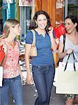 Trois femmes à l'extérieur, porter les sacs et souriant