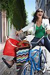 Femme en plein air à vélo avec les sacs à provisions souriant