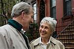 A senior couple outside of a brownstone