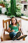 Portrait de jeune fille assise dans une chaise à l'extérieur
