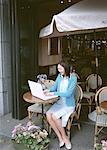 Femme utilisant un ordinateur portable au café en plein air