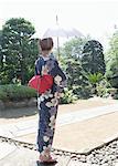 Femme habillée Yukata holding parasol