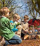 Trois garçons à genoux autour de feu de camp cuisson du poisson