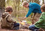 Trois garçons autour d'ébullition de l'eau dans une bouilloire de feu de camp