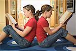 Jumelles adolescent assis dos à dos lors de la lecture.