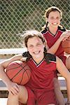 Twin teen girls holding basketballs.