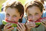 Twin teenage girls eating slices of watermelon.