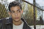 Portrait d'un adolescent à une clôture.