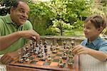 Senior homme jouant aux échecs avec son jeune petit-fils.