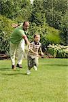 Grand-père jouant avec son petit-fils de jeunes au parc.