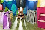Image rognée d'une femme debout parmi les sacs à provisions.