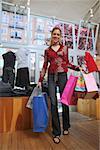 Jeune femme de race blanche dans la boutique de sacs à provisions.