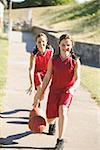 Teen girls dribbling basketballs