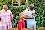 Couple hugging at family picnic