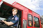 Female firefighter sitting in fire truck