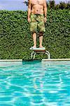 Homme debout sur le plongeoir de piscine