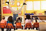 Male teacher doing handstand in classroom