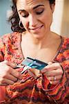 Femme, découpage de la carte de crédit