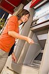 Vue d'angle faible de la femme à l'aide d'ATM