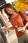Femme souriant et à l'aide d'ATM