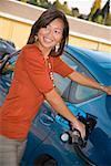 Femme gaz de pompage à la station service