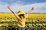 Jeune fille debout dans le champ de fleurs jaunes