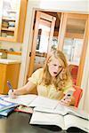 Adolescente en étudiant et en regardant de téléphone cellulaire