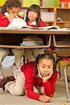 African girl sitting under school desk