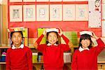 Multi-ethnic girl balancing school books on heads