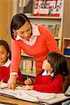 African female teacher helping student