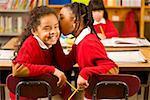 African girls telling secret in classroom