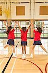 Multi-ethnic girls jumping in school gym