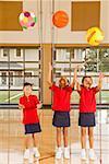 Multi-ethnic girls throwing sports balls