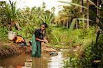 Femme faisant la lessive dans les cours d'eau, Cochin, Kerala, Inde