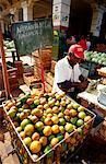 Man Peeling Oranges at Market, Havana, Cuba