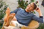Porträt von Mann, sitzend mit Füße hoch im freien
