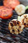 L'ail et les tomates sur une grille de barbecue